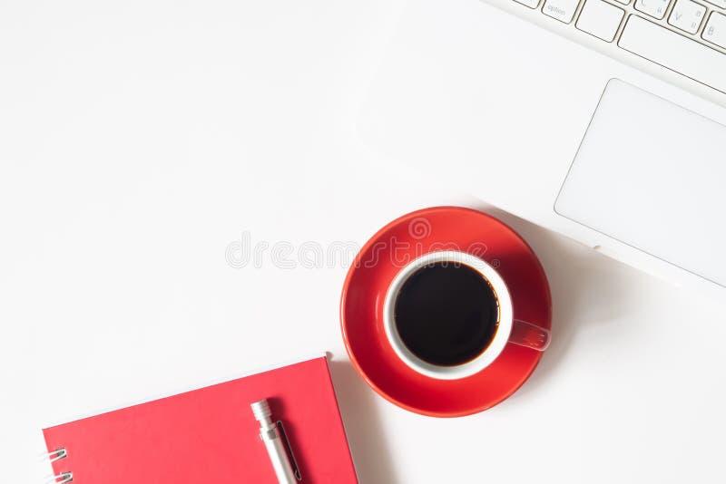 Место для работы домашнего офиса с красными чашкой кофе, компьтер-книжкой и noteboo стоковые изображения