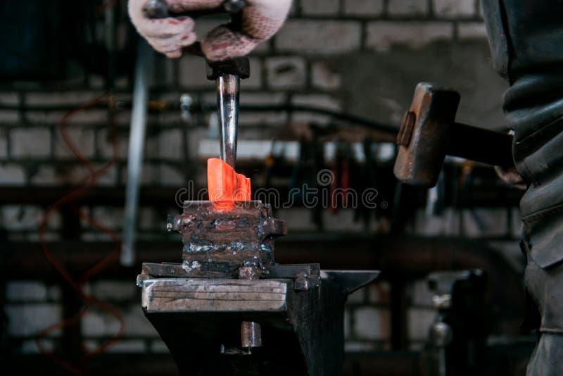 Место для работы кузнеца Кузнец работая с накаленным докрасна металлом на наковальне в кузнице стоковое изображение