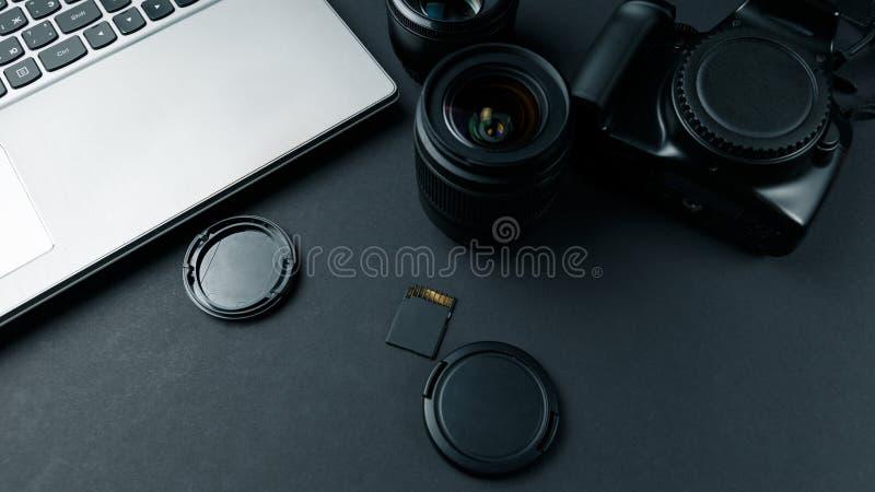 Место для работы на черной таблице фотографа Минимальное место для работы с космосом экземпляра ноутбука, камеры и объектива на т стоковая фотография rf