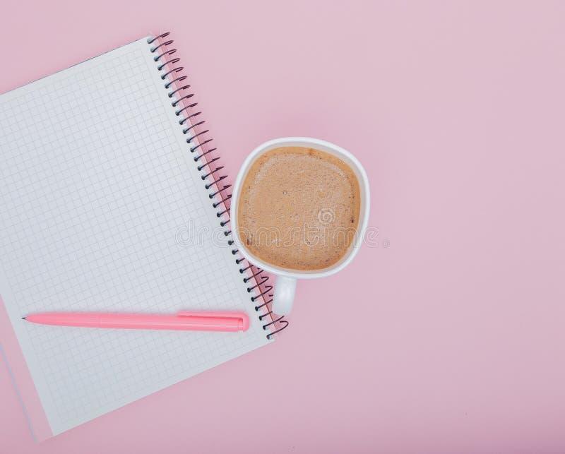 Место для работы предпосылки дела взгляд сверху с кофе, ручкой и пустой тетрадью на розовой предпосылке изображение для образован стоковые изображения rf