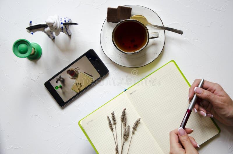 Место для работы с блокнотом, чашкой чаю на белой предпосылке Плоское положение, стол сочинительства стола офиса взгляда сверху Ф стоковое фото
