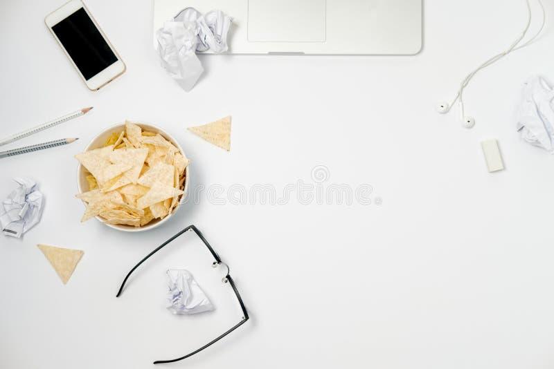 Место для работы с компьтер-книжкой, скомканной бумагой, канцелярскими принадлежностями и обломоками стоковое изображение