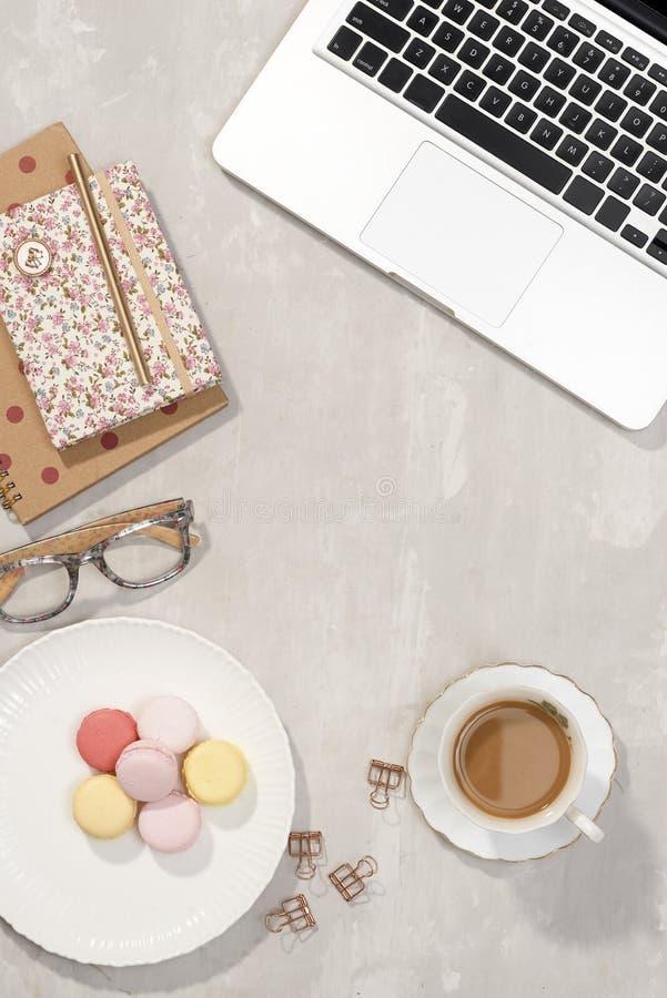 Место для работы с ноутбуком, тетрадью, стеклами, чашкой кофе и цветками lisianthus на серой предпосылке Таблица офиса взгляда св стоковые фото