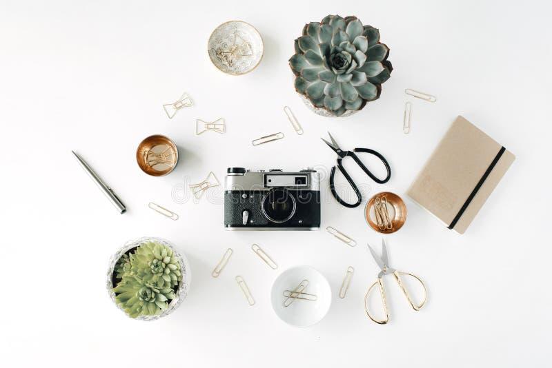 Место для работы стола Feminini с суккулентной, ретро камерой, ножницами, дневником и золотыми зажимами на белой предпосылке стоковые фотографии rf