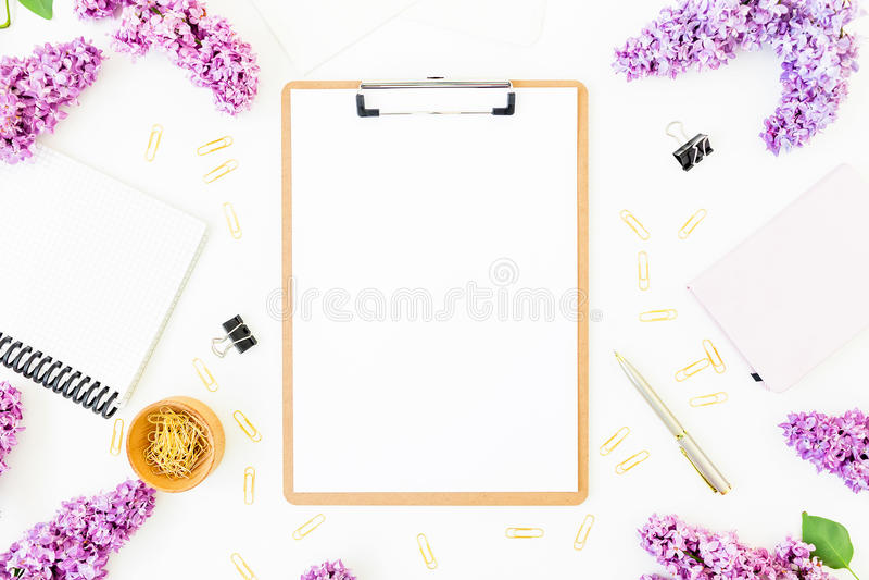 Место для работы Minimalistic с доской сзажимом для бумаги, тетрадью, ручкой, сиренью и аксессуарами на белой предпосылке Плоское стоковое изображение
