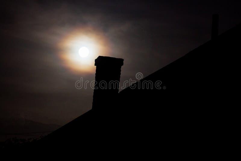 Месяц над домом, ночью полнолуние сияет над домом, рождественская звезда над домом стоковая фотография