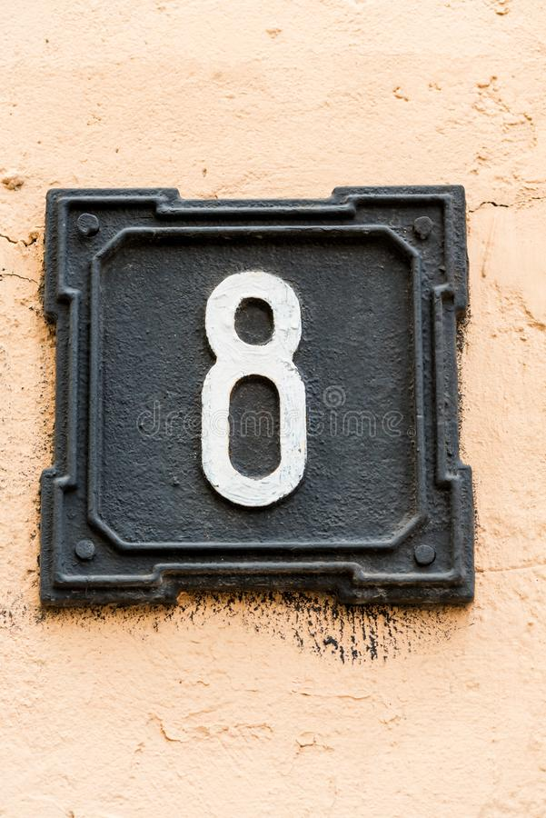 Металлический номер дома, чернит на стене стоковая фотография rf