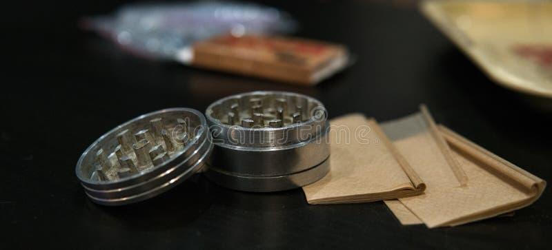 Металлический серебряный точильщик для бутонов марихуаны nlying на дыме завертывает конец-вверх в бумагу Узаконьте концепцию стоковое изображение rf