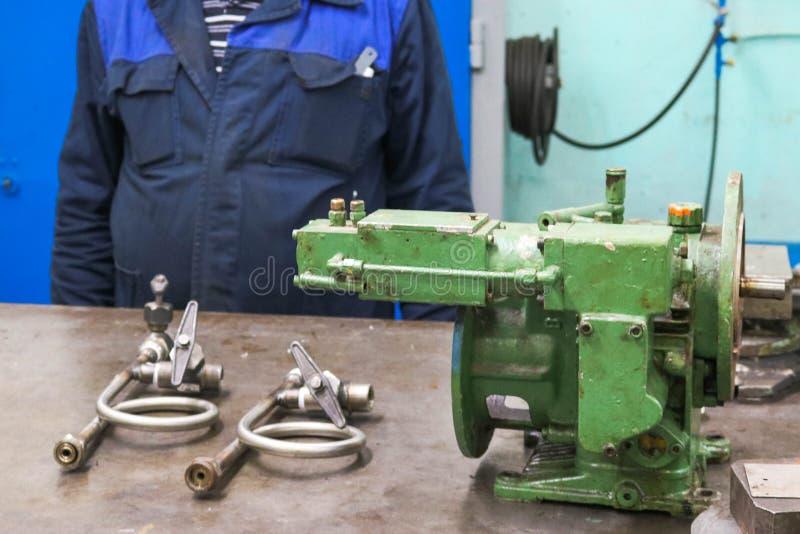 Металлический чугунный промышленный насосный плунгер, центробежный и манометрический агрегат в металлической мастерской на столе  стоковая фотография