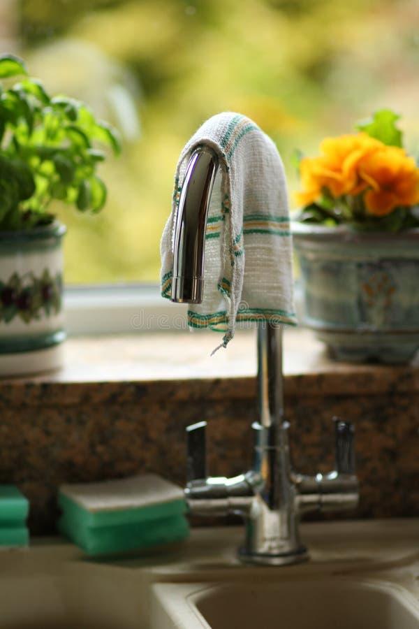 Металлическое крана кухни прикрепленное над раковиной в домашнем конце кухни вверх стоковое изображение