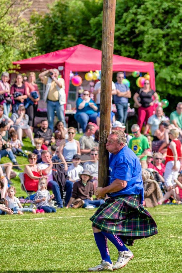 Метать дисциплина caber на шотландских играх гористой местности стоковое фото rf