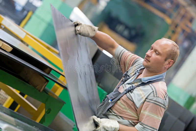 Металлический лист заводской рабочий moving в мастерской стоковые изображения