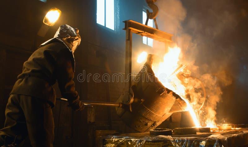Металл работника контролируя плавя в печах Работники работают на металлургическом предприятии стоковая фотография rf