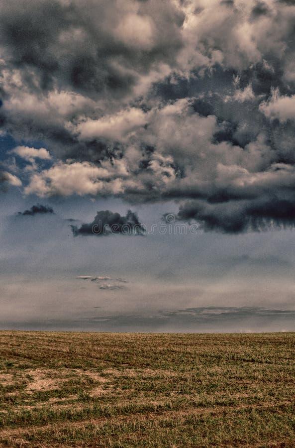 Метеорологическое фото - драматические темные сложные кучевые облако над земледелием field в лете Горизонт, расслабляющее mystiqu стоковые изображения