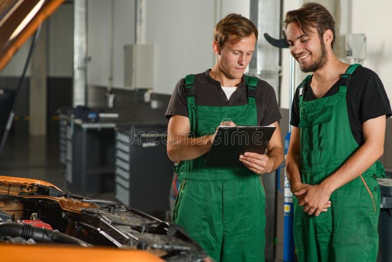 2 механика прочитали техническую документацию около автомобиля стоковое изображение