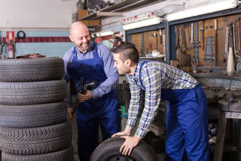 Механики автомобиля работая на carshop стоковое изображение
