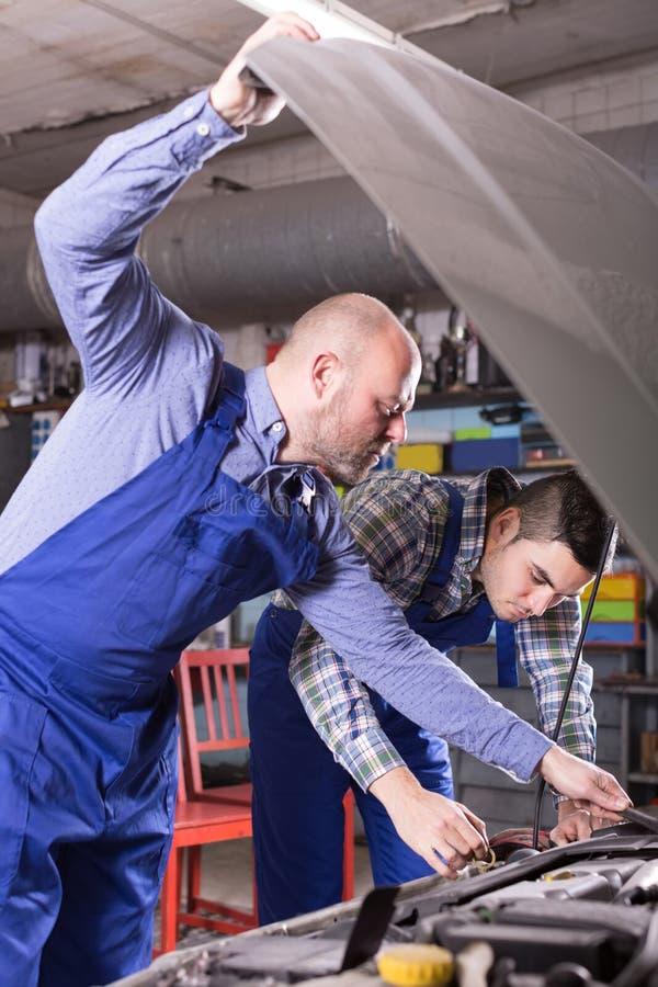 Механики автомобиля работая на carshop стоковое фото rf