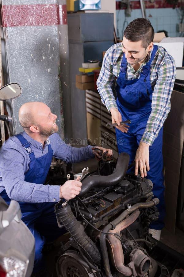 Механики автомобиля работая на carshop стоковое изображение rf