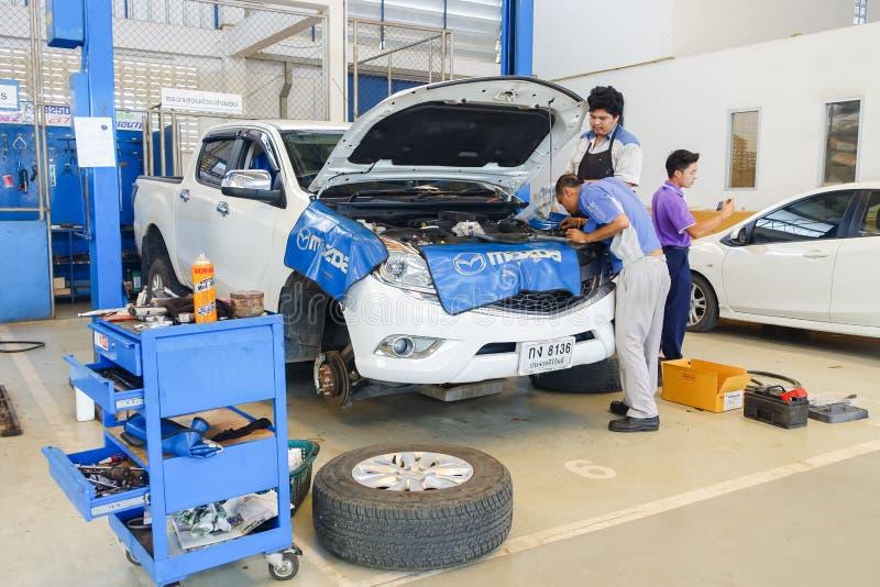 Механики исправляя автомобиль стоковая фотография