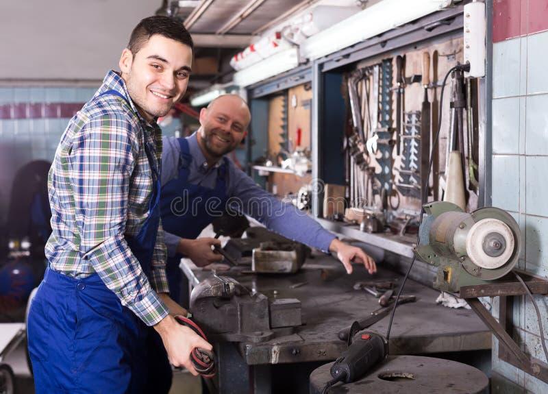 Механики работая с инструментами стоковое фото