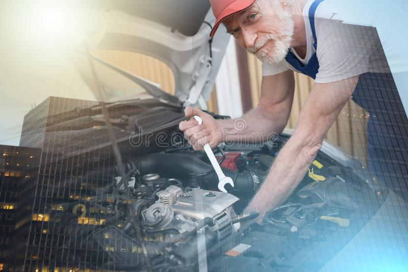 Механик автомобиля работая на двигателе автомобиля; множественная выдержка стоковая фотография