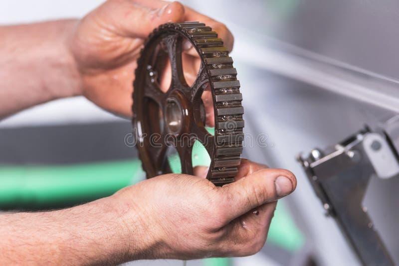 Механик автомобиля, чистка и mantaining шестерня стоковая фотография