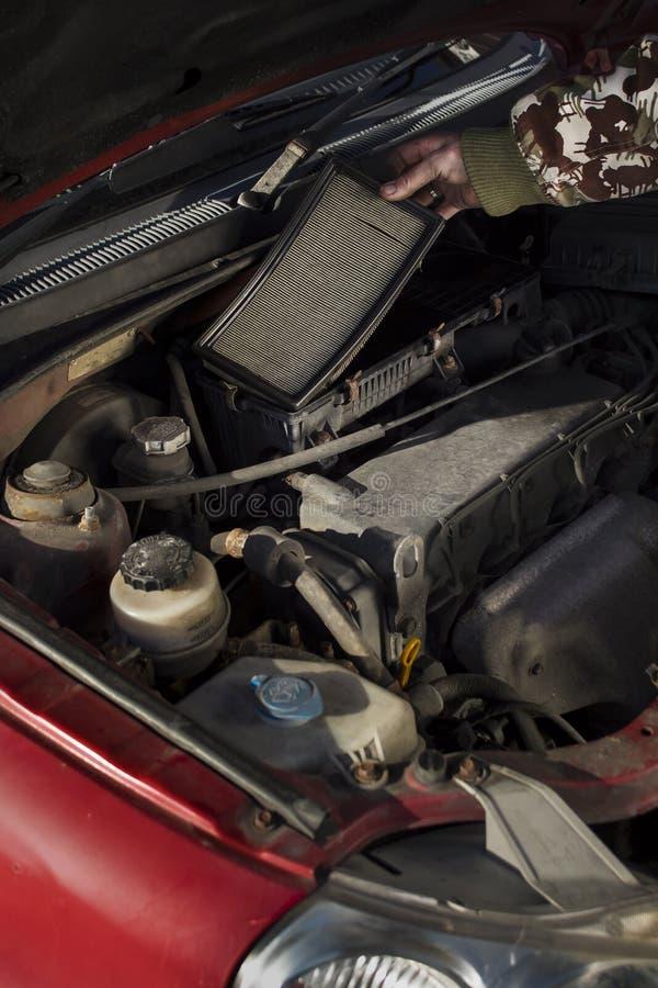 Механик вытягивает вне старый воздушный фильтр Заменять воздушный фильтр в вашем автомобиле стоковая фотография rf