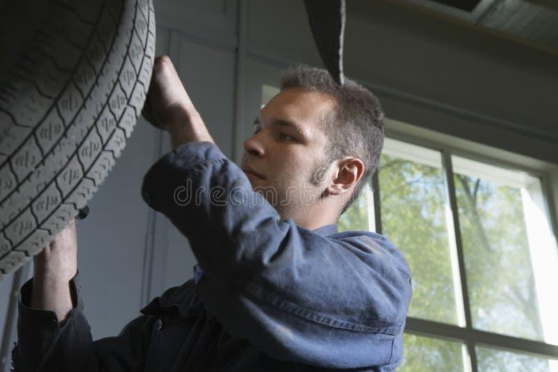 Механик изменяя автомобиль катит внутри гараж стоковое изображение