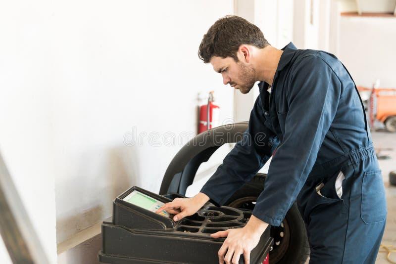 Механик используя машину балансера колеса в ремонтной мастерской автомобиля стоковая фотография rf