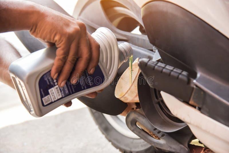 Механик лить новое масло двигателя к двигателю мотоцикла стоковые фотографии rf