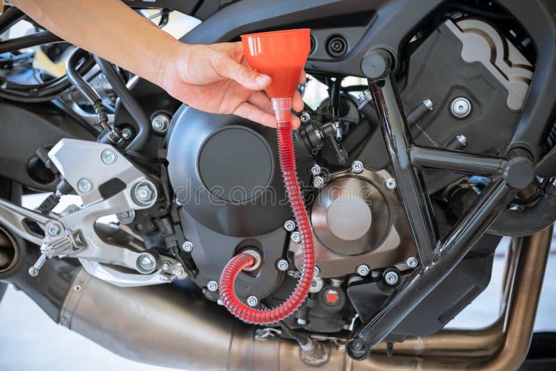Механик лить свежее масло будучи политым во время изменения масла к двигателю мотоцикла стоковые изображения