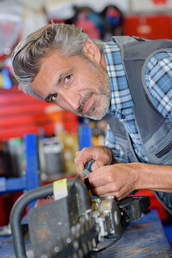 Механик портрета работая на триммере изгороди стоковая фотография