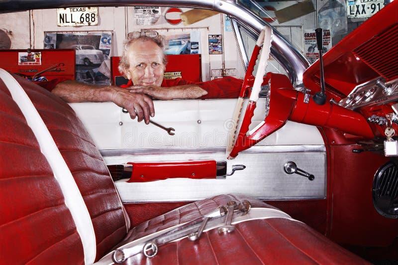 Механик полагаясь над окном автомобиля в гараже стоковые фотографии rf
