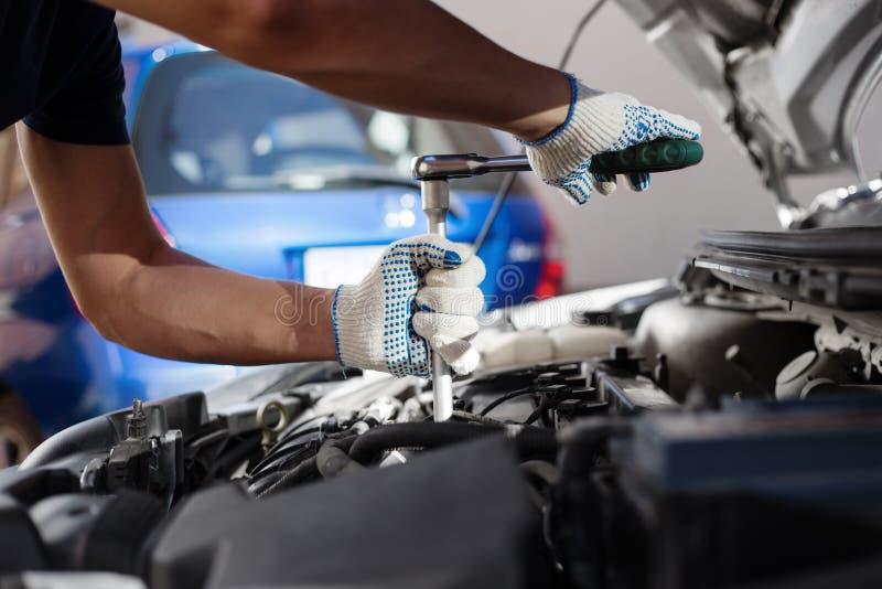 Механик работая в гараже ремонта автомобилей Обслуживание автомобиля стоковая фотография rf