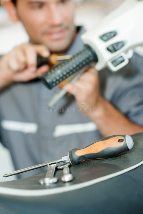 Механик работая на самокате handlebars стоковая фотография