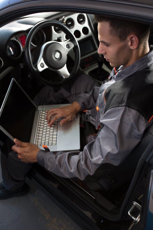 Механик смотря диагностический компьютер стоковые фотографии rf