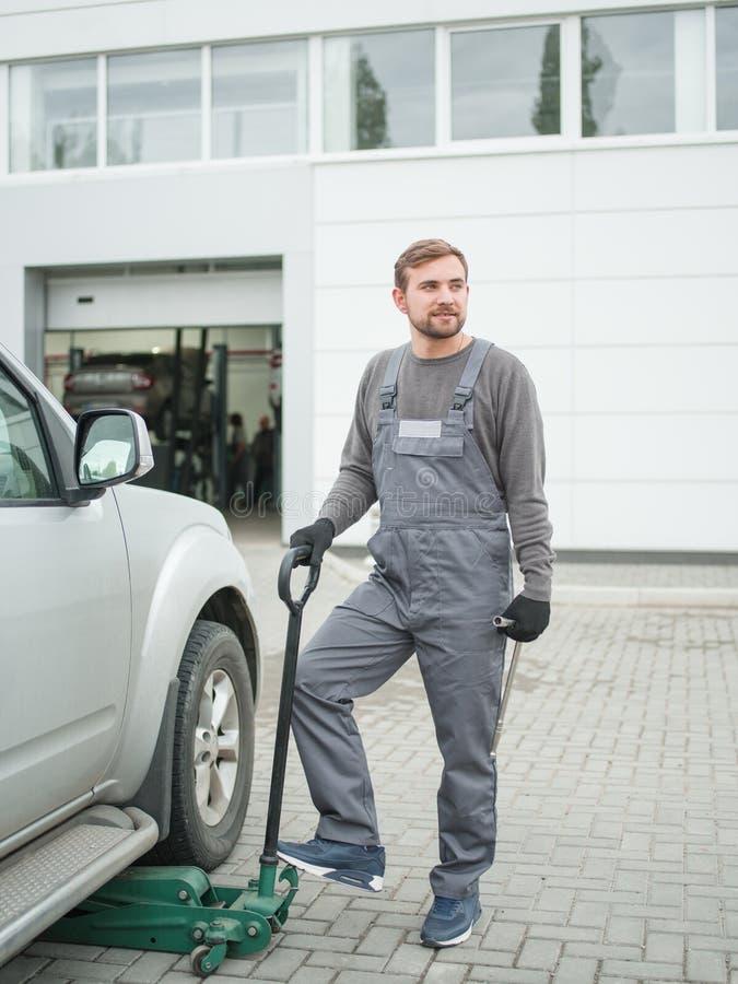 Механик стоит около автомобиля и держит Джек-винт outdoors стоковое изображение rf