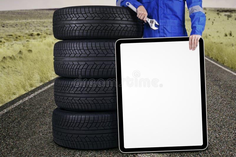 Механик с автошинами и доска outdoors стоковое изображение