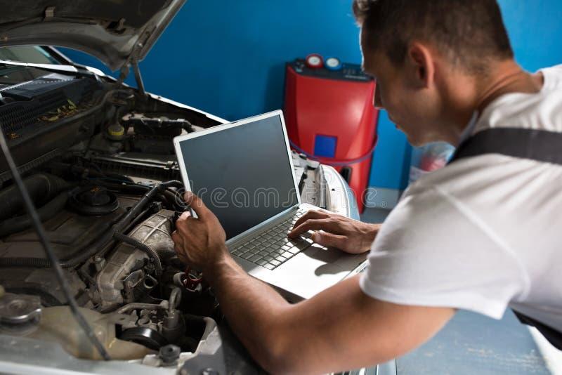 Механик с диагностическим инструментом в мастерской автомобиля стоковое фото rf