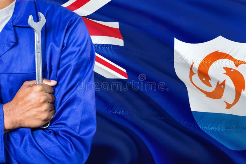 Механик Anguillian в голубой форме держит ключ против развевать предпосылка флага Ангильи Пересеченный техник оружий стоковое фото rf