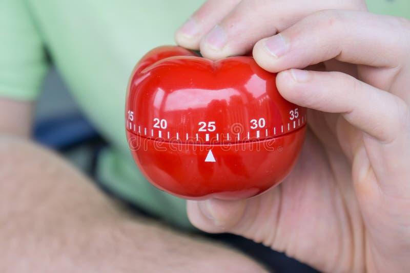 Механический красный таймер кухни томата установил до 25 минут, сжатых одной рукой стоковые изображения rf