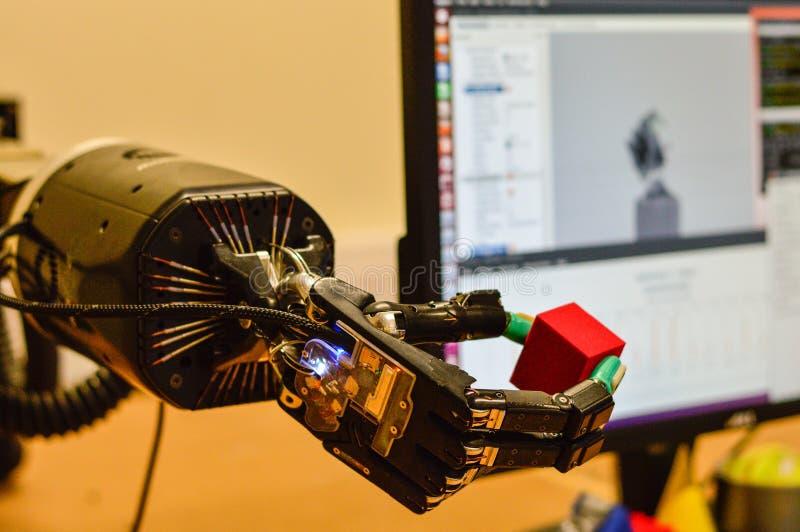 Механически рука робота держит красный куб в исследовательской лабаратории стоковое фото rf