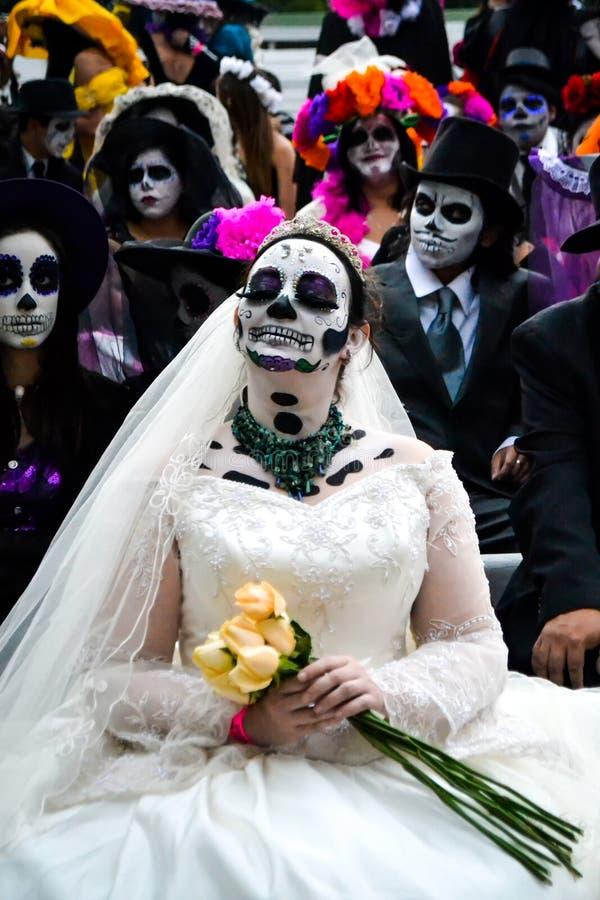 Мехико, Мексика; 1-ое ноября 2015: Невеста окруженная черепами на дне мертвого торжества в Мехико стоковое изображение