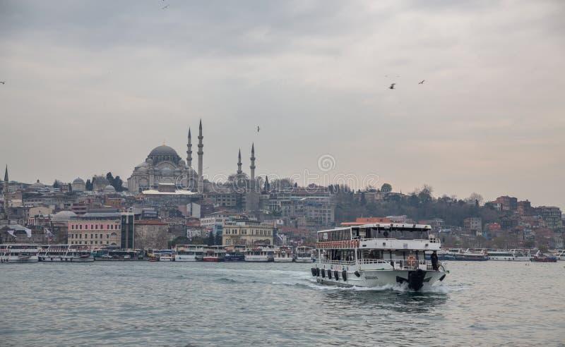 Мечеть и туристская шлюпка в Стамбуле против облачного неба стоковое изображение rf