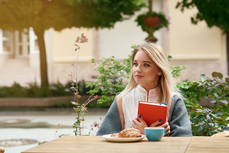 Мечтательная белокурая девушка держа Красную книгу сидеть outdoors стоковая фотография