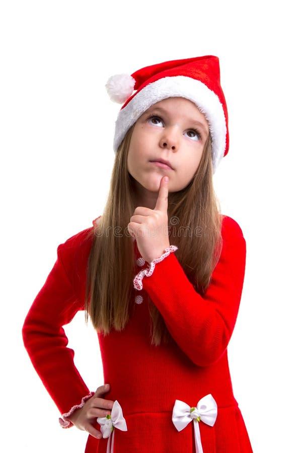 Мечтательная девушка рождества нося шляпу santa изолированную над белой предпосылкой стоковая фотография