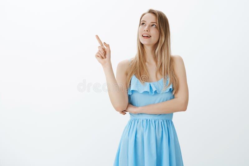 Мечтательная девушка считая звезды Нежная и милая молодая европейская женщина со справедливыми волосами в голубом платье указывая стоковые фото
