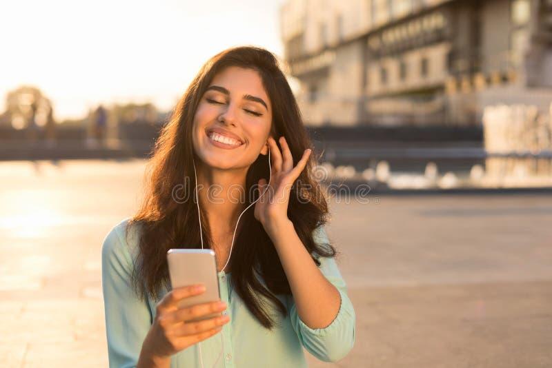 Мечтательная женщина наслаждаясь музыкой в наушниках outdoors стоковая фотография rf