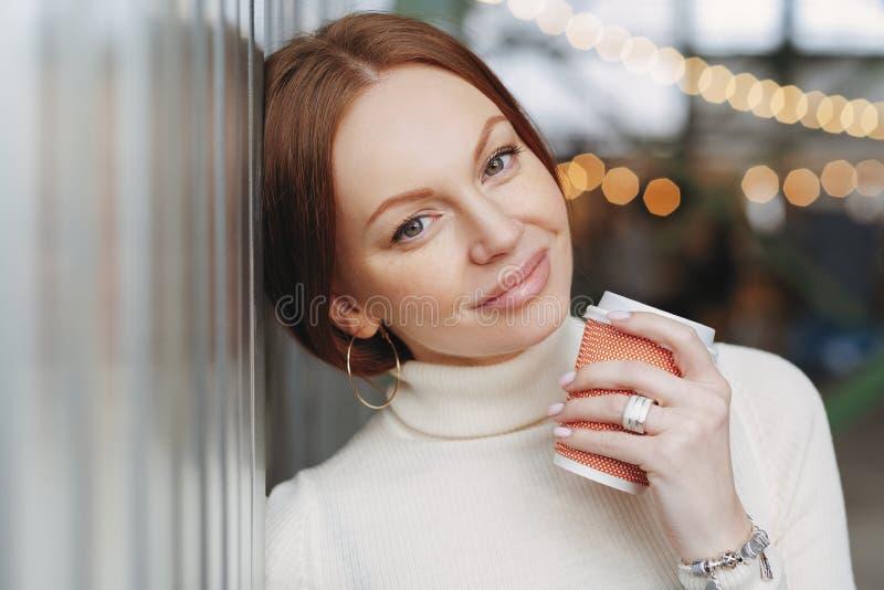 Мечтательная задумчивая кавказская женщина с составляет, одетый в случайном обмундировании, полагается на стене, держит на вынос  стоковое фото