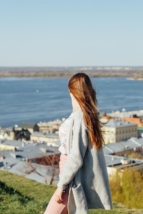 Мечтательная милая женщина сидя рекой города стоковые фотографии rf